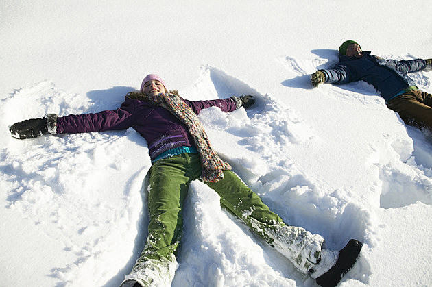 Grandfather and granddaughter (12-14) making snow angels, smiling